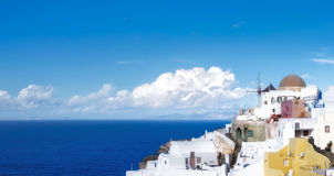 Traditional windmill and apartments in Oia village on a sunny d Royalty Free Stock Images