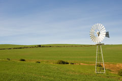Traditional windmill in a green pasture. A traditional windmill turning in the wind and pumping water out of the ground into a catchment dam Royalty Free Stock Photos