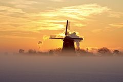 Traditional windmill in snow in Netherlands. Traditional windmill in snow and fog in the countryside from the Netherlands at sunset Stock Photos