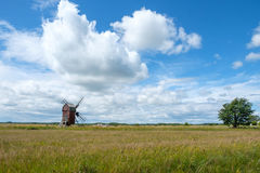 "Traditional windmill on Swedish island Oland. In the Baltic Sea. Windmills are a common sight on Oland, which is nicknamed ""the island of the sun and stock photography"