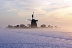 Traditional windmill in winter in the Netherlands. Traditional windmill at twilight with fog and snow in winter in the Netherlands Royalty Free Stock Image