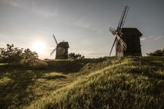 Traditional windmills on grassy hills at sunset Stock Photography