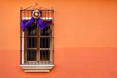 Traditional window on orange wall with semana santa ribbon decoration in Antigua, Guatemala. Traditional window on orange wall with purple white semana santa stock photo