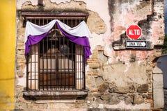 Traditional window with semana santa ribbon decoration in Antigua, Guatemala. Traditional window with purple white semana santa easter ribbon decoration in royalty free stock photos