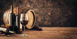 Traditional winemaking and wine tasting. Wine glass, wooden barrel and collection of excellent red wine bottles in the cellar: traditional winemaking and wine Stock Images
