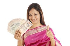 Traditional woman holding Indian currency. Happy young traditional woman holding Indian currency and making thumbs up gesture Stock Photo