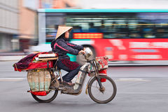 Traditional woman transports stuff on an electric bike, Kunming, china. KUNMING-JULY 5, 2014. Woman transports stuff on electric bike. Motorized bikes in Chinese royalty free stock photo