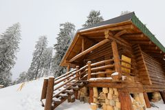 Traditional wood alpine chalet on a mountain slope against forest royalty free stock photo