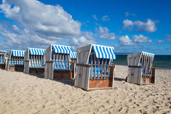Traditional wooden beach chairs on Rugen island,Germany. Sandy beach and traditional wooden beach chairs on Rugen island, Northern Germany, on the coast of royalty free stock images