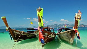 Traditional wooden boat with ribbon decoration at ocean shore under blue sky.Thailand stock video