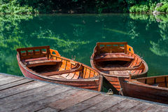Traditional wooden boats at forest lake pier Stock Image