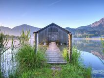 Traditional wooden boats old house at the alpine lake royalty free stock photo