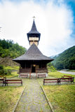 Traditional wooden church in the mountains against a cloudy sky Royalty Free Stock Photos