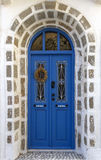 Traditional wooden door in Greece. Typical, traditional wooden made door in the village of Nikia, in the island of Nisyros, in Greece. The arch is made of stone Stock Images