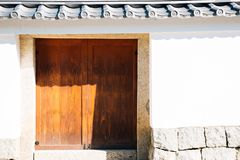 Traditional wooden door and wall in Kyoto, Japan. Traditional wooden door and white wall in Kyoto, Japan royalty free stock images