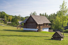 Traditional wooden farm house on meadow Stock Images