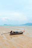 Traditional wooden fishing boat on the deserted sandy sea shore Stock Image