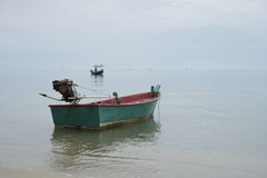 Traditional wooden fishing boat floating on the peace surface wave of the seas,in the afternoon against the blue water. S,selective focus Stock Photo