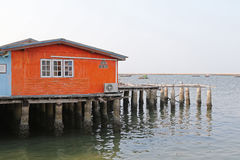 Traditional wooden house of fisherman in orange built on concret Royalty Free Stock Images