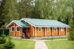 Traditional wooden house on green field in summer the background of forest Royalty Free Stock Images