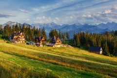 Traditional wooden house in the mountains on a green field Mount Royalty Free Stock Photo