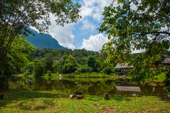 Traditional wooden house near the lake and mountain in the background. Kuching to Sarawak Culture village. Borneo, Malaysia Stock Photos