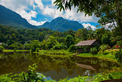 Traditional wooden house near the lake and mountain in the background. Kuching to Sarawak Culture village. Borneo, Malaysia Stock Images