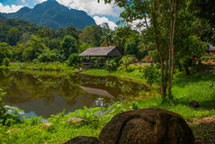 Traditional wooden house near the lake and mountain in the background. Kuching to Sarawak Culture village. Borneo, Malaysia Royalty Free Stock Images