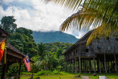 Traditional wooden house near mountain in the background. Kuching to Sarawak Culture village. Borneo, Malaysia Stock Photos