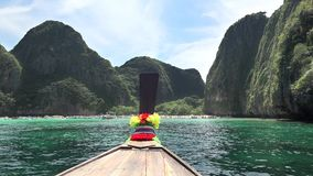 Traditional wooden long-tail boat enters Maya Bay in Phi Phi Islands, Andaman Sea, Thailand stock footage