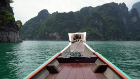 Traditional Wooden Longtail Boat Nose. Front View at Limestone Cliffs Rising from the Water at Cheow Lan Lake in. Thailand, Khao Sok National Park shot with stock video footage