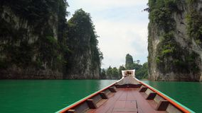 Traditional Wooden Longtail Boat Nose. Front View at Limestone Cliffs Rising from the Water at Cheow Lan Lake in. Thailand, Khao Sok National Park shot with stock footage