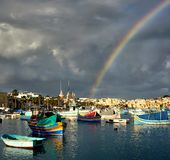 Stormy day in Marsaxlokk harbor, heavy clouds and rainbow royalty free stock photos