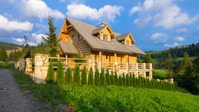 Traditional wooden mountain house built from wood logs on summer Royalty Free Stock Photos