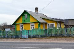 Traditional wooden rural house in Belarus, rural winter landscape with street and road. Traditional wooden house in Belarus, rural winter landscape with street stock photos