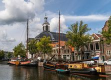 Traditional wooden sailing ships in water channel. Church on background. Old historic harbor of Schiedam, The. Traditional wooden sailing ships in a water royalty free stock image