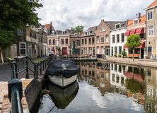 Traditional wooden sailing ships in water channel. Old historic harbor of Schiedam, The Netherlands. Traditional wooden sailing ships in a water channel. Old royalty free stock image