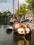 Traditional wooden sailing ships in water channel. Old historic harbor of Schiedam, The Netherlands stock photography
