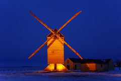 Traditional wooden windmill. Night image of an old traditional wooden windmill in a field covered by snow.This windmill is The big windmill from Ouarville from Stock Images
