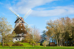 Traditional wooden windmill in a lush garden Royalty Free Stock Photography