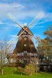 Traditional wooden windmill in a lush garden Royalty Free Stock Image
