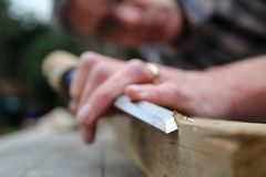 Traditional woodworker using wooden mallet and chisel.  Royalty Free Stock Images