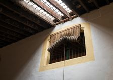Traditional woven rush blind covering window. Traditional rolled and woven rush fabric blind covering window in old warehouse or winery Stock Images