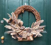 Traditional xmas wreath on front door. Traditional design of a christmas wreath attached to the front door of old house Stock Photography