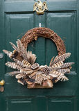 Traditional xmas wreath on front door. Traditional design of a christmas wreath attached to the front door of old house Stock Image