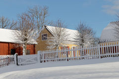 Traditional yellow and red houses in the wintry landscape Stock Photo