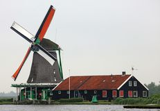 Traditional zaanse schans windmill in The Netherlands. Unique beautiful and wild European city. Amsterdam, The Netherlands, city canals, boats, bridges and Royalty Free Stock Photo