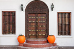 Traditional zanzibar door. Traditional zanzibar wooden door and doorway ornately carved and decorated with pots Royalty Free Stock Image