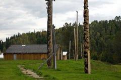 Traditionall Gitxsan totem poles and longhouse Stock Photo