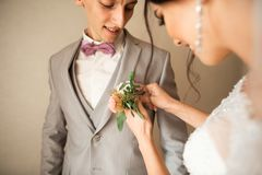 Traditionally, the bride in the house touches a small bouquet for the groom. Groom bouquet next to the hand on suit.  stock image